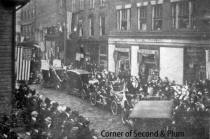 Crystal Pharmacy in background of parade dated by cars shown as early 1900s.