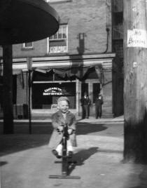 Unknown child riding toy in front of Marraccini's Market with Post Office across the street