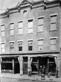 "Exterior of the building is from collection of John Dziama. Note store front to the left of Wylie Bros. is the original State Bank shown in photos below in their ""new"" location."