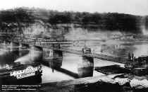 This photo, taken approximately 1880, shows the work in progress of replacing the old suspension bridge with the current Smithfield St. Bridge. The current bridge was built above and around the old bridge. The photo also shows the Packet Geneva in the foreground.