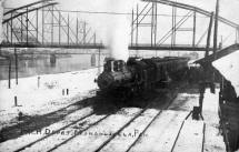 "The signifiances of this train station photo is that it shows the ""new"" bridge and the ""old"" bridge in the background.  The photo can be dated as probably late 1909 or early 1910, winter snow on ground."